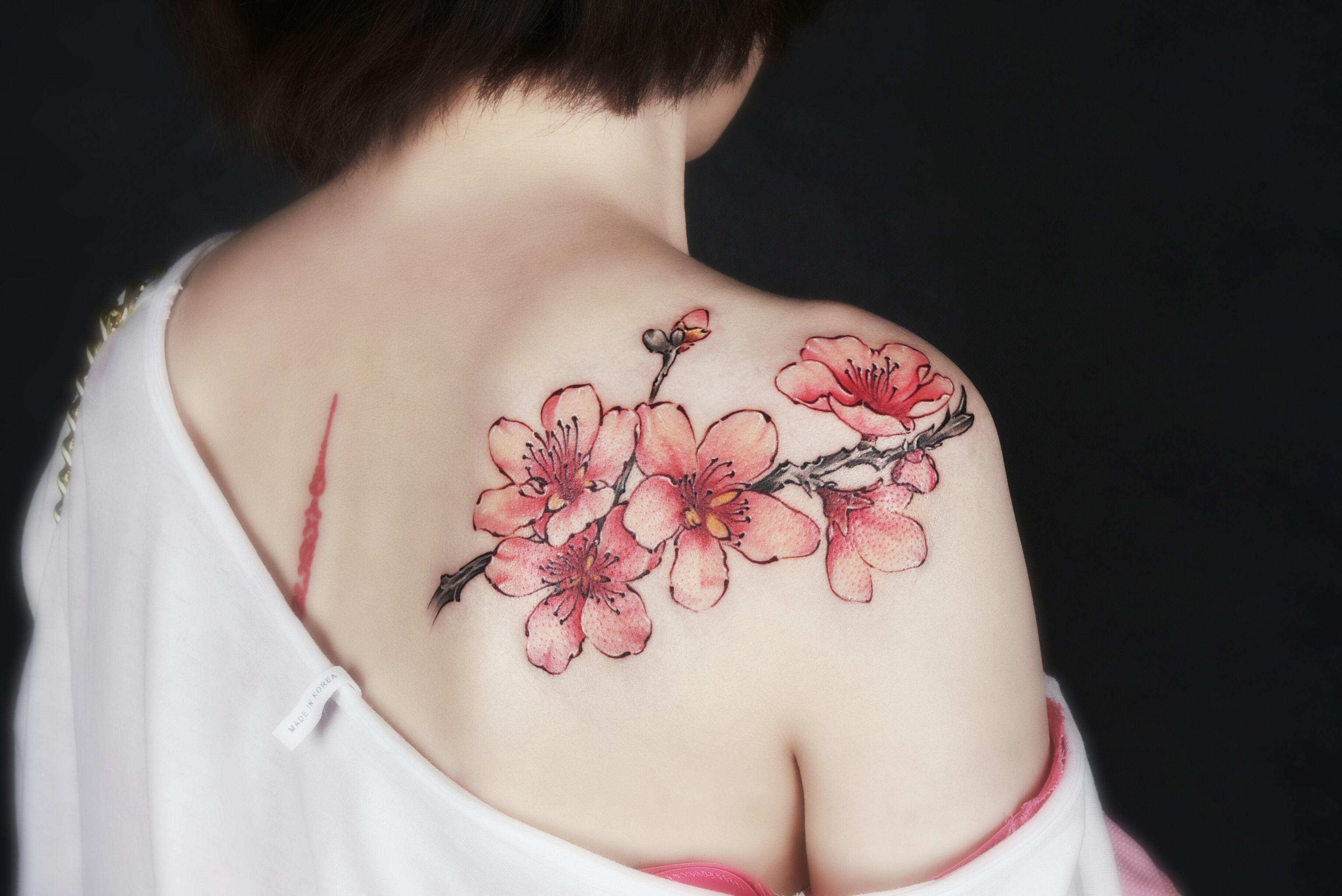 樱花花瓣圆润、花色大多是浪漫的粉色系, 尤其在初春盛开时,一片片樱花林总能带给人幽香艳丽的视觉享受, 且樱花花期非常短暂,甚至一场雨后,花瓣就会随风凋零, 因此樱花也被人们赋予了热烈、纯洁、高尚的美好品质。 我们天津的美女董小姐,正是被樱花的浪漫艳丽, 以及热烈、高尚的品质所吸引, 因此特别将樱花用纹身的方式,呈现在自己皮肤上。 且董小姐的这个纹身图案,我们纹身师在设计时, 将含苞待放的花骨朵以及已经完美盛开的樱花, 同时呈现在黑色的枝桠上, 更衬托出了初樱的明动艳丽。